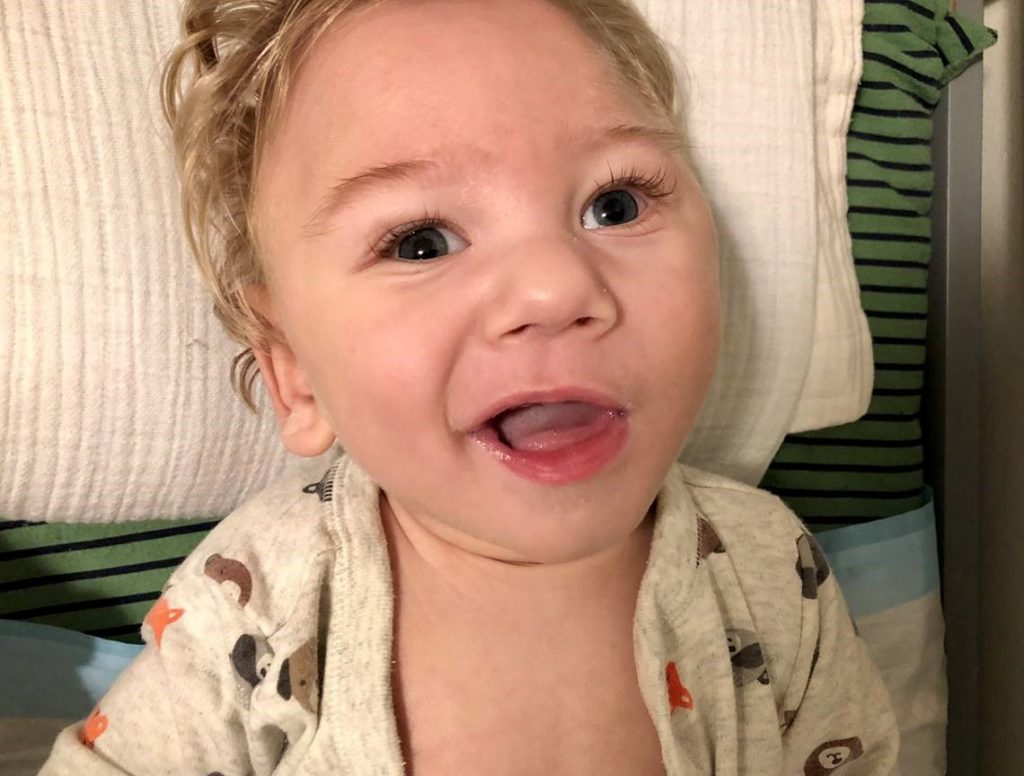 Smiling Baby laying on pillow receiving pediatric hospice care